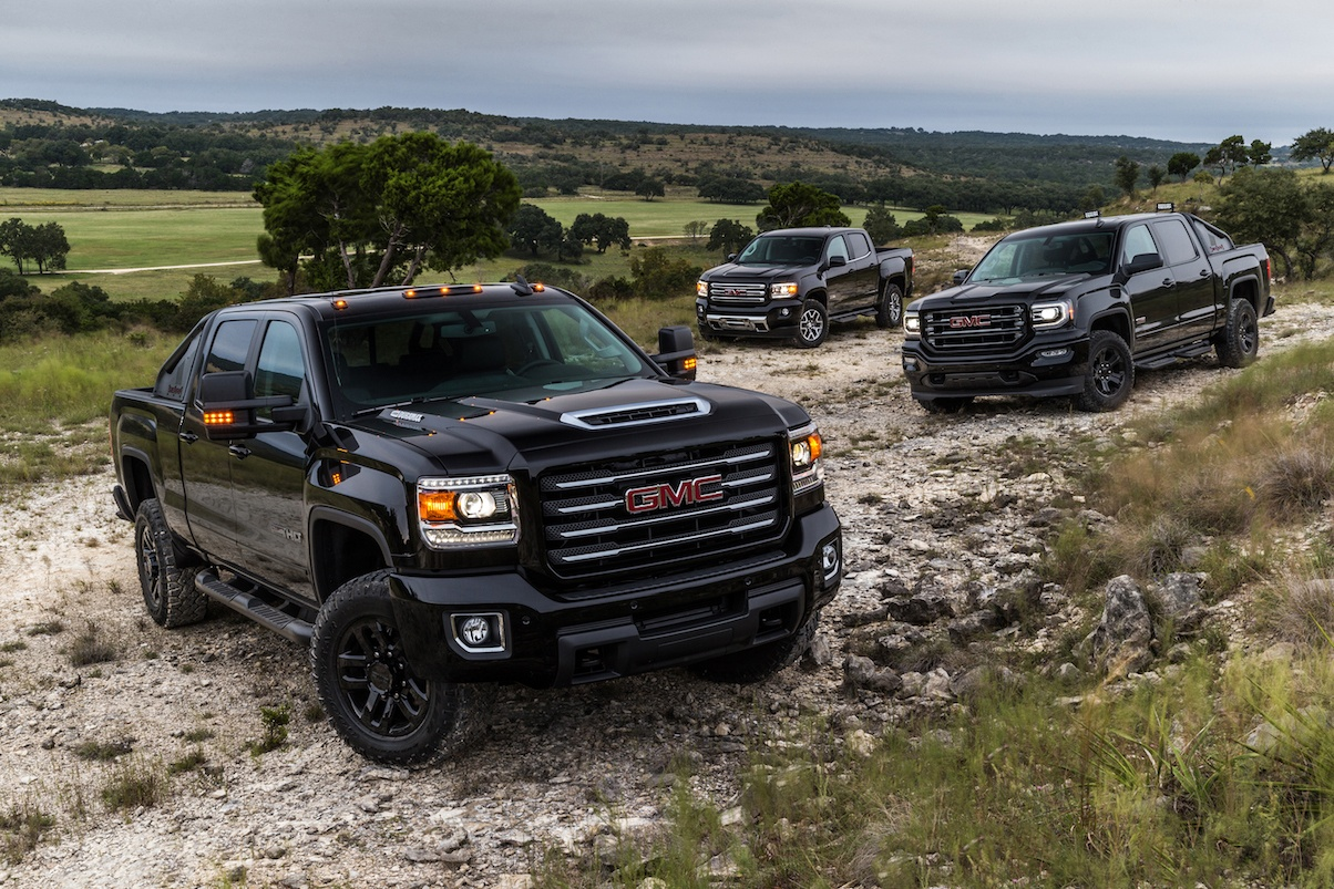 Three black GMC pick-up trucks parked on a rocky road.