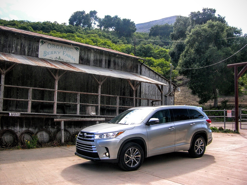 Silver 2017 Toyota Highlander parked in front of a store.