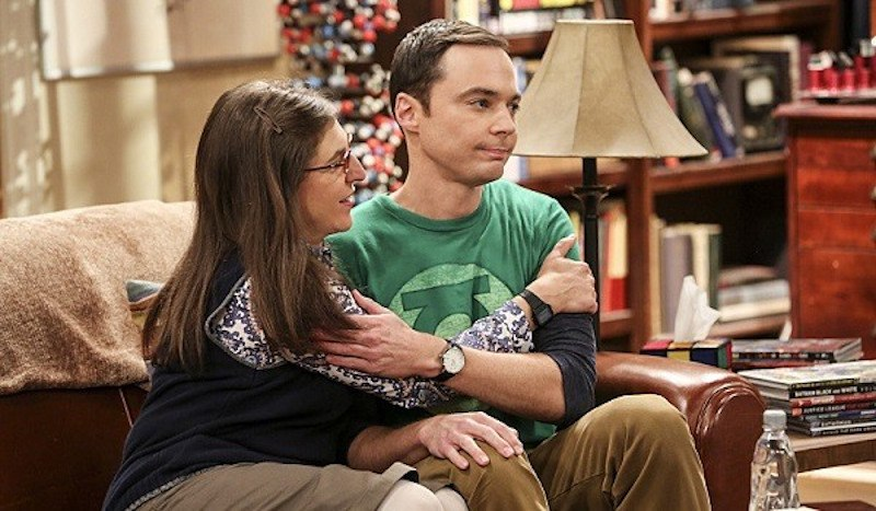 Amy and Sheldon hug on a couch in The Big Bang Theory