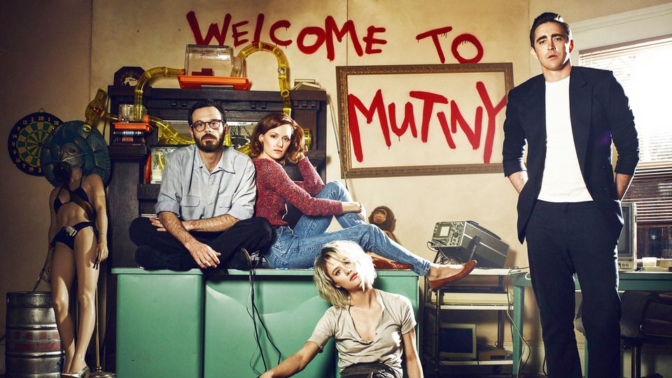 The cast of 'Halt and Catch Fire' in a messy room with the words 'Welcome to Mutiny' spray painted behind them.