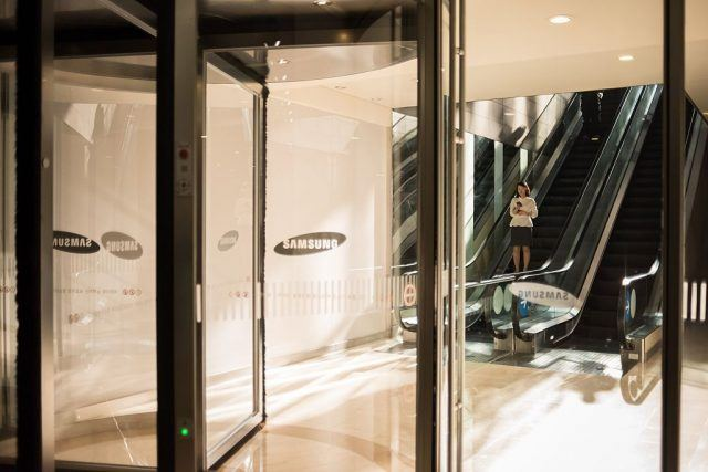 A woman looks at a mobile phone as she stands on an elevator in a mall beneath the Samsung headquarters