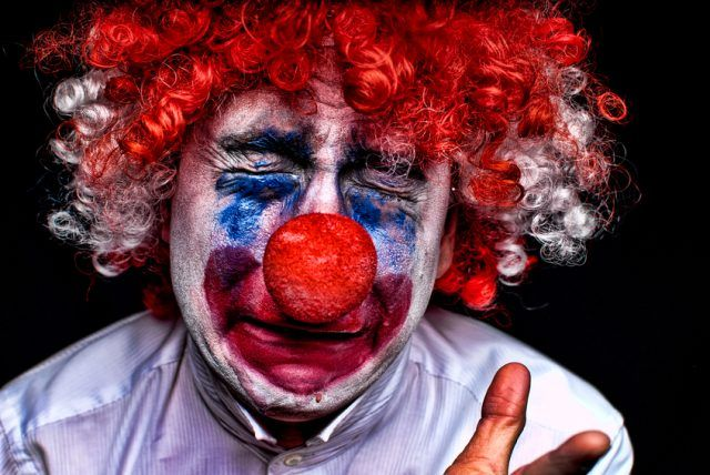 A clown pictured behind a black background.