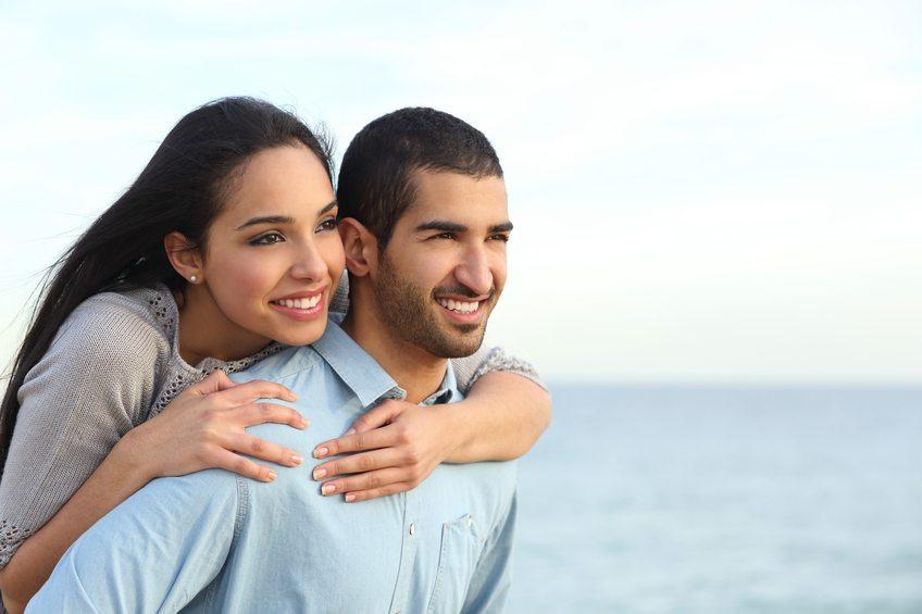 Arab couple flirting piggyback in love on the beach