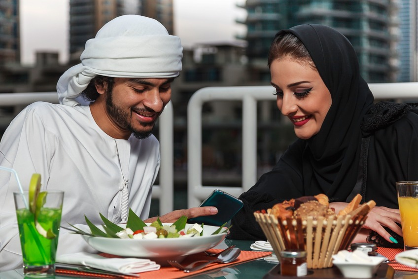 Arab couple looking at their mobile phone