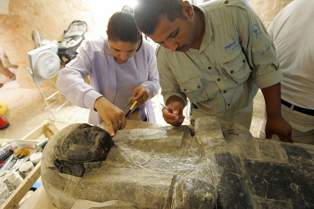 archaeologists work in Egypt on a sarcophagus