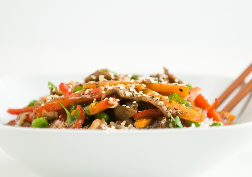 Asian beef stir-fry on rice with peppers carrots