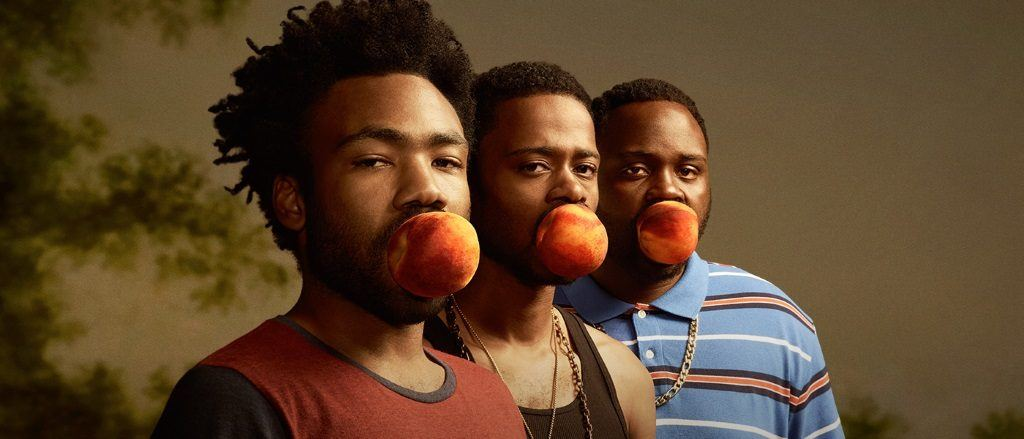 3 men holding peaches in their mouths
