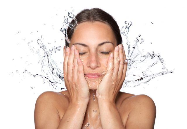 woman washing her face