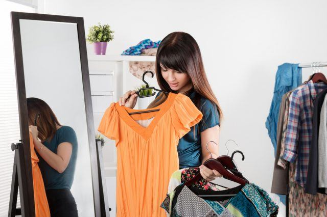 young woman near rack with clothes