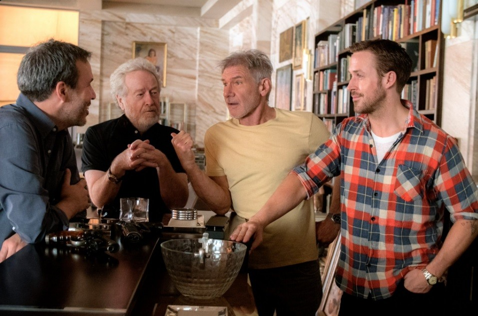 Denis Villeneuve, Ridley Scott, Harrison Ford, and Ryan Gosling stand around a counter