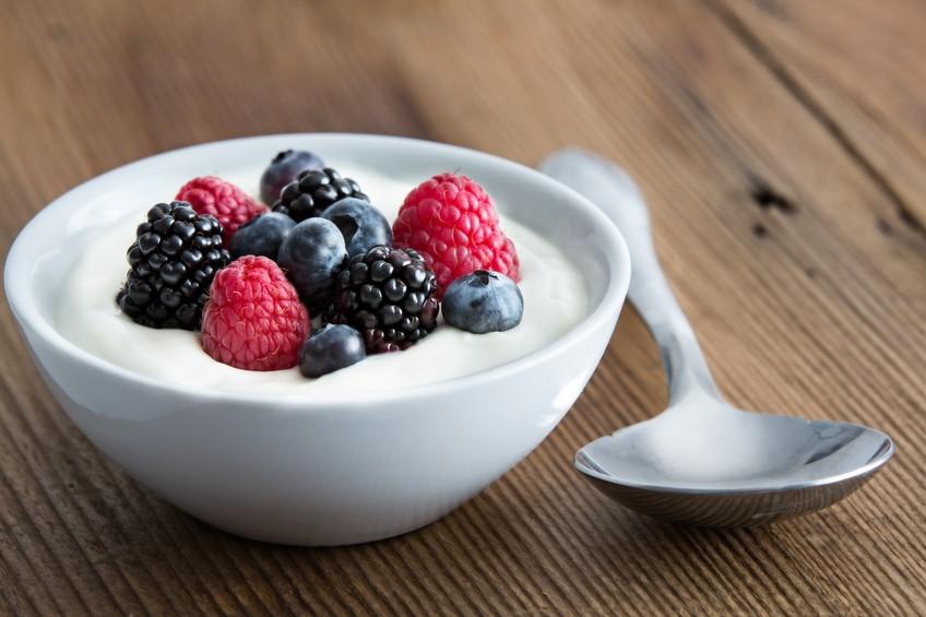 Bowl of fresh mixed berries and yogurt with farm fresh strawberries