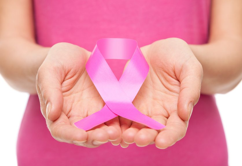 Woman holding a pink breast cancer awareness ribbon