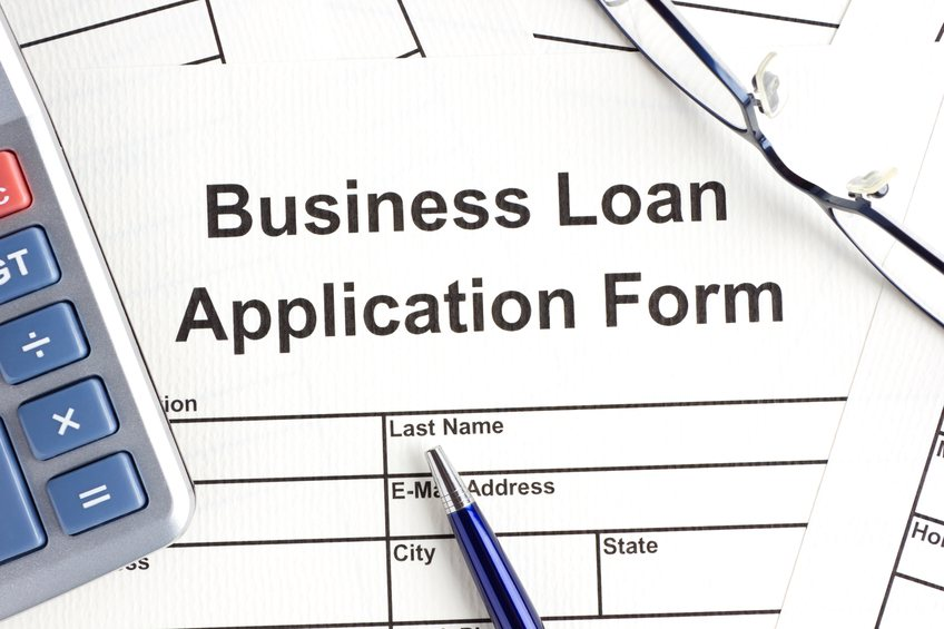 Business loan application form with pen and a calculator