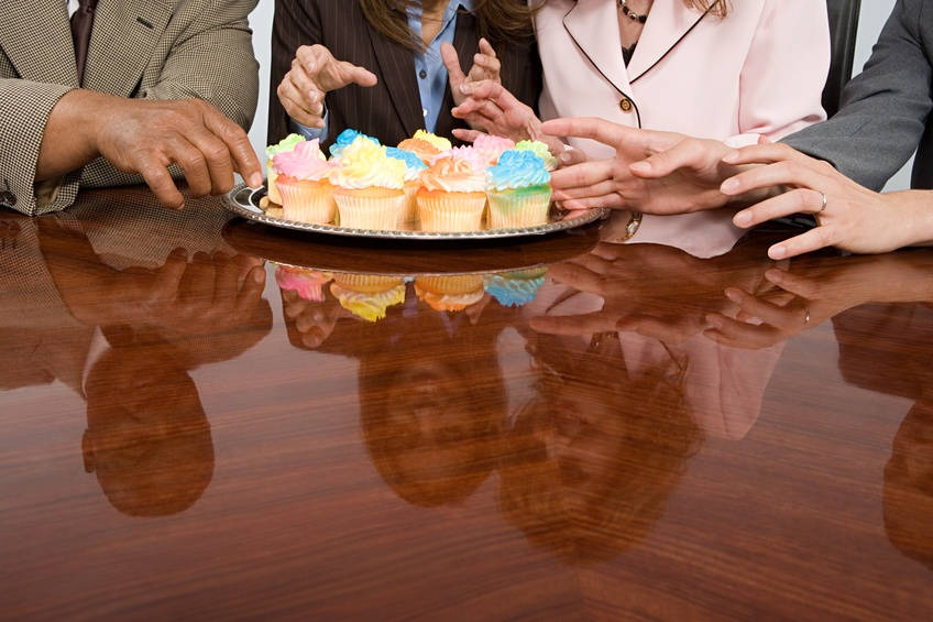 Businesspeople eating cupcakes