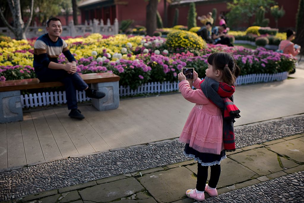 A young girl takes a photo of her dad with a smartphone