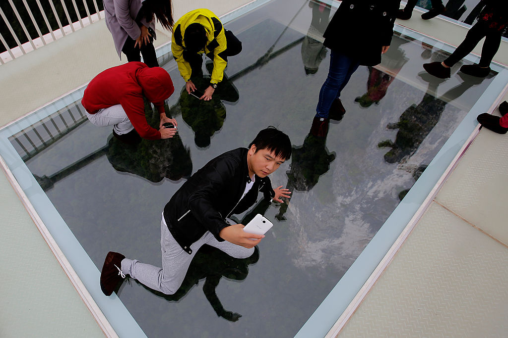 Tourists take pictures with their iphone on the glass-floor