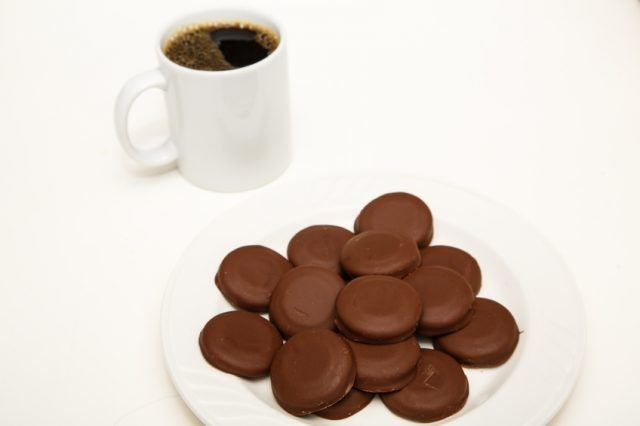 A white plate of chocoloate covered mint cookies with cup of coffee