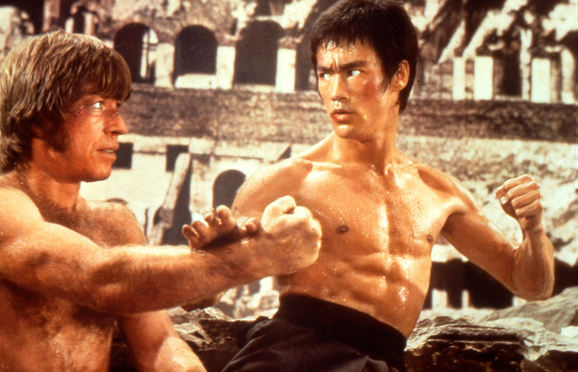 Chuck Norris and Bruce Lee fighting each other in the Roman Colosseum