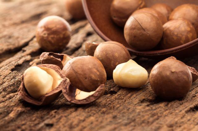 A close up shot of macadamia nuts laid out on a wooden table.
