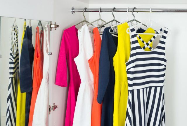 a series of bright modern fashion women's dresses on hangers