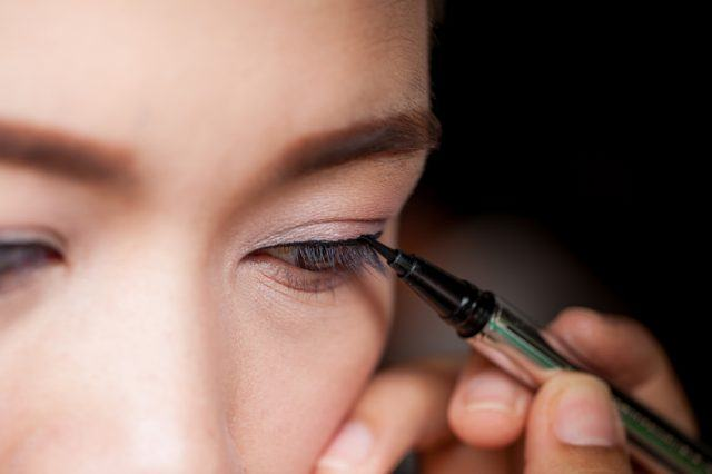 asian woman applying eyeliner on eye
