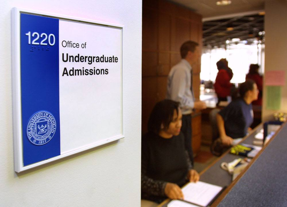 Workers staff the front desk of the University of Michigan's Undergraduate Admissions office