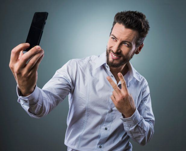 Man taking self portraits with his smartphone