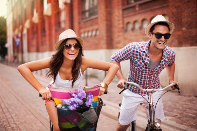 A couple riding bicycles in the city after meeting on an online dating platform
