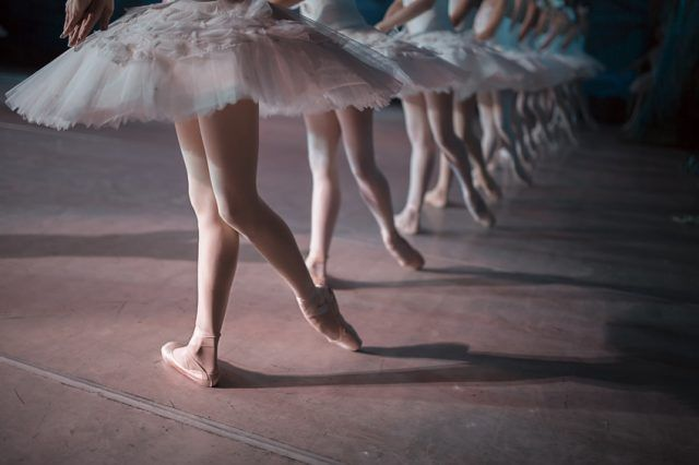 Dancers in white tutu synchronized dancing on stage