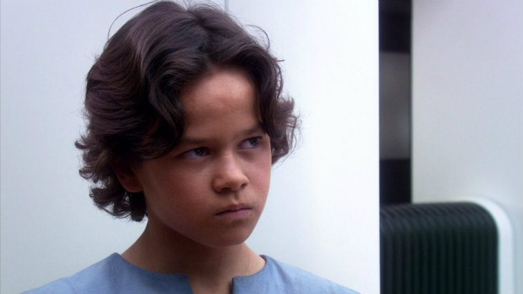 Daniel Logan in Star Wars: Attack of the Clones, wearing a blue tunic and scowling, looking upwards defiantly