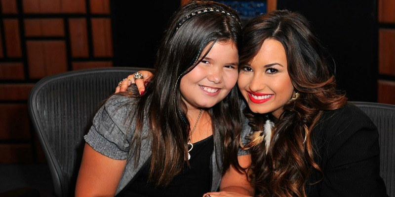 Demi Lovato and Madison De La Garza are sitting next to each other and are smiling.