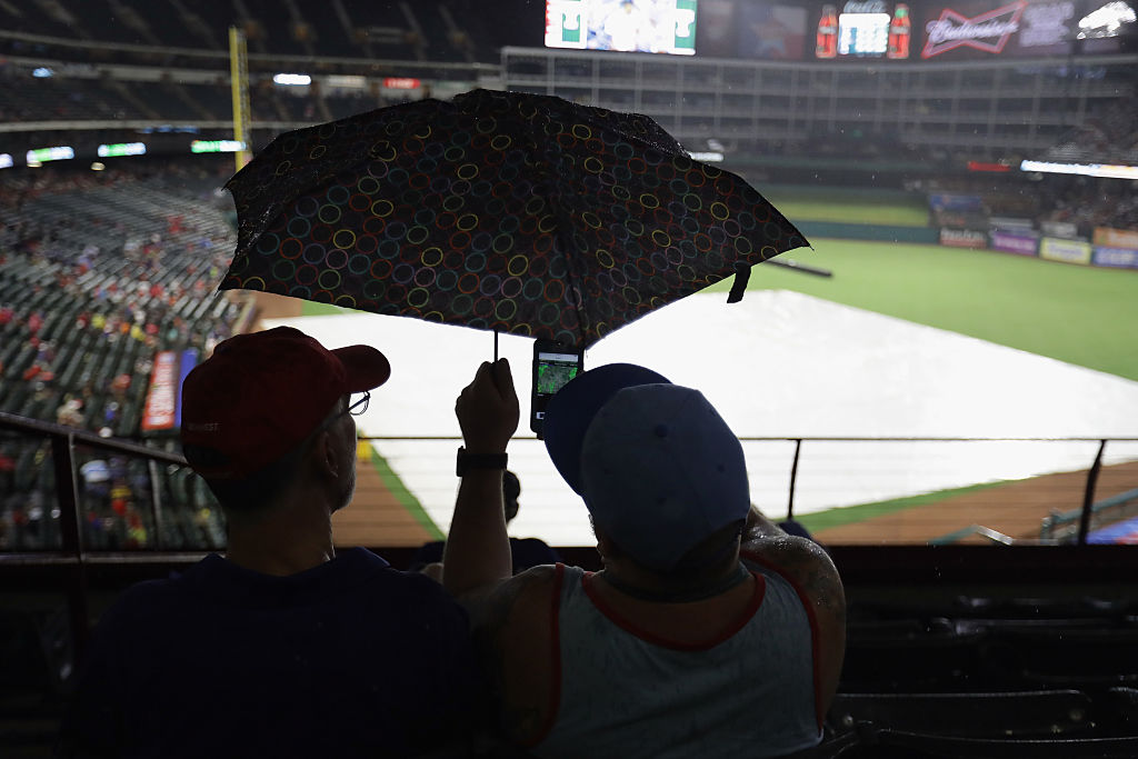 Fans look at the weather radar on a smartphone during a rain delay
