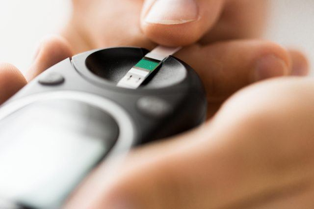 man checking blood sugar level by glucometer