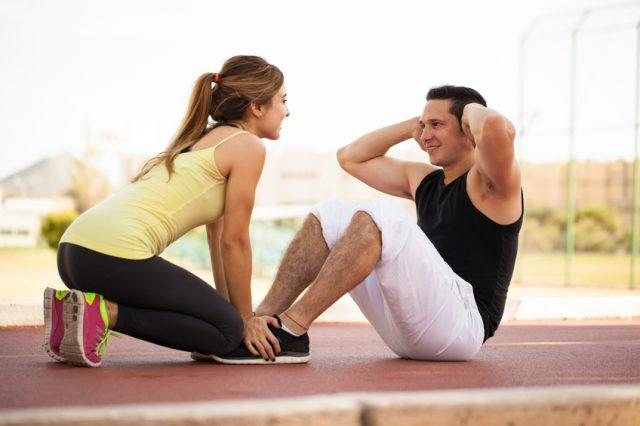 Girl helping and motivating her boyfriend do some crunches