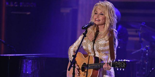 Dolly Parton playing a guitar and singing.