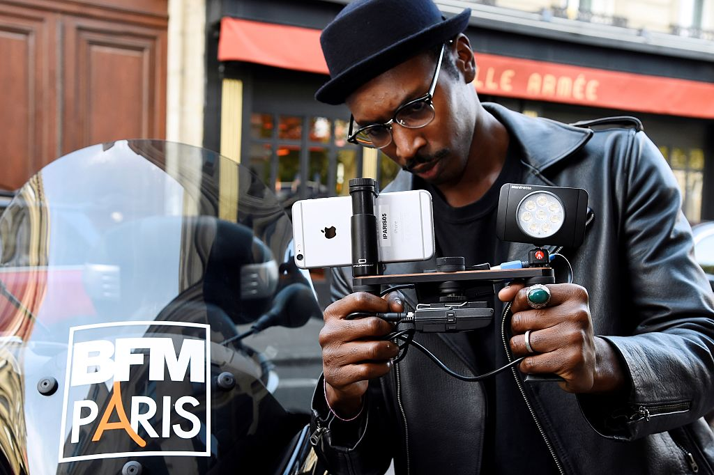 A journalist holds a shoulderpod, a tripod mount adapter with an Iphone smartphone