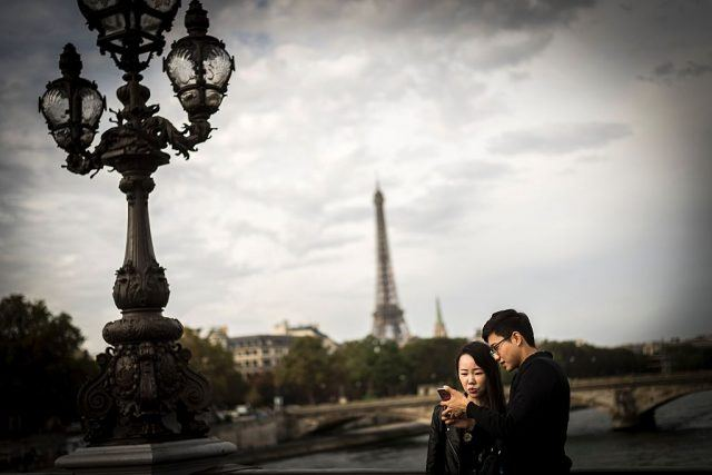 A young couple looks at a smartphone in front of the Eiffel Tower
