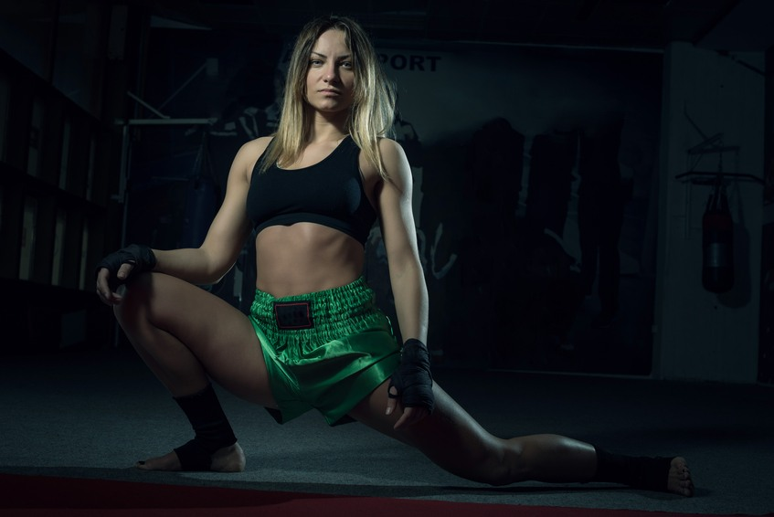 Young adult kickboxing girl stretching her body
