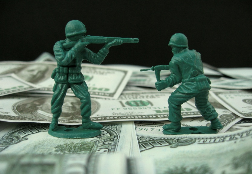 Two toy soldiers fighting over dollar bills -- a fun metaphor for purchasing power and money valuation