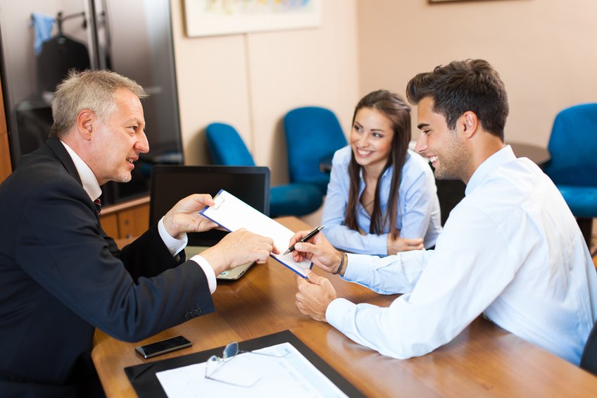 businessman showing a document to sign to a couple