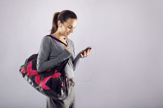 Female athlete with a sports bag listening to music on her mobile phone.