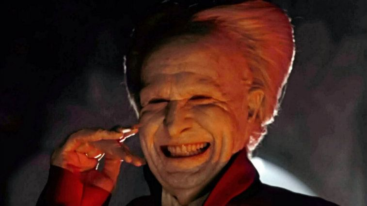 Gary Oldman with his hand to his face, smiling ear to ear in Dracula