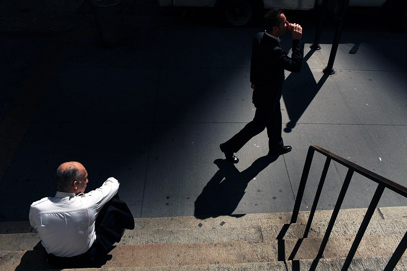 A businessman walks along Wall Street in front of the New York Stock Exchange