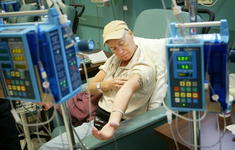 A patient inspects their arm during treatment