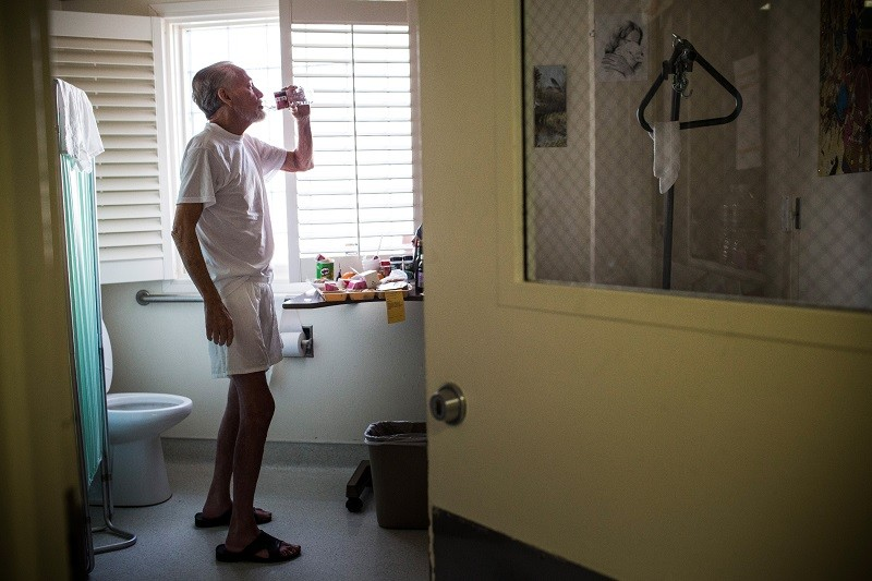 An older cancer patient drinks water near a bathroom