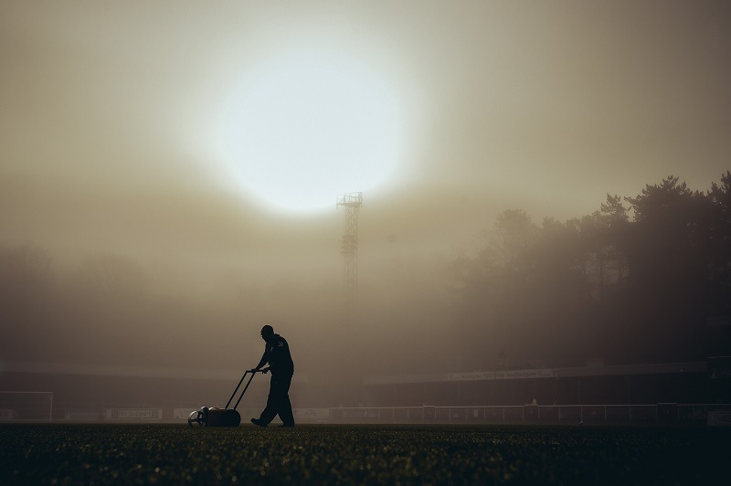 A working class groundsman prepares an athletic field