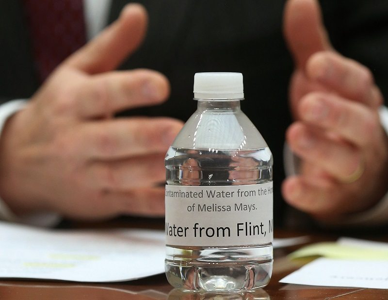 WASHINGTON, DC - A bottle of contaminated Flint tap water -- drinking water responsible for lead poisoning -- sits on the witness table during a hearing on the Flint, Michigan water crisis03: A bottle of contaminated Flint tap water sits on the witness table while Rep. Dan Kildee (D-MI) speaks, during a House Oversight and Government Reform Committee hearing on the Flint, Michigan water crisis on Capitol Hill February 3, 2016 in Washington, DC. The committee heard testimony on the Federal Administration of the Safe Drinking Water Act in Flint, Michigan. (Photo by Mark Wilson/Getty Images)