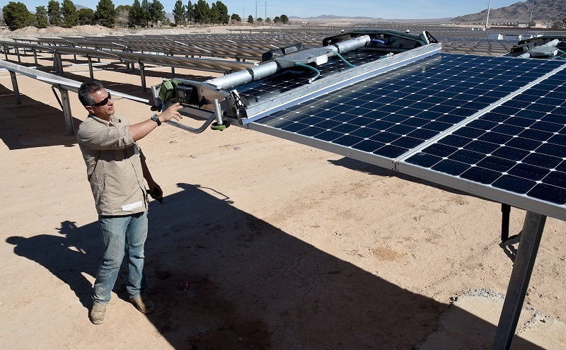 LAS VEGAS, NV - FEBRUARY 16: SunPower field supervisor Oscar Madrigal demonstrates using a panel washing robot on a row of solar panels during a dedication ceremony to commemorate the completion of the 102-acre, 15-megawatt Solar Array II Generating Station at Nellis Air Force Base on February 16, 2016 in Las Vegas, Nevada. When coupled with the 13.2-megawatt Nellis Solar Star project completed in 2007, Nellis has the largest solar photovoltaic system in the Department of Defense. During daylight hours the two solar fields combined provide almost all of the base's energy needs or about 42 percent of its overall electricity requirements. Power from the array that is not used will go to the NV Energy grid and back into the local community. (Photo by Ethan Miller/Getty Images)