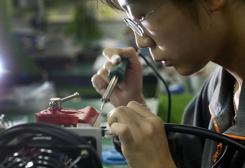 A factory worker makes parts at a joint venture Chinese and Japanese electronics firm