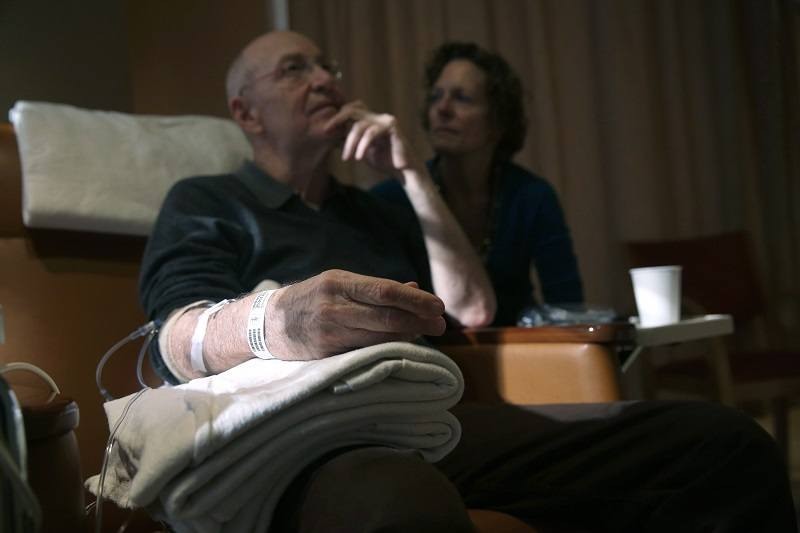 A man sits while undergoing chemotherapy cancer treatment as his wife looks on